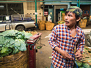 "11 AUGUST 2016 - BANGKOK, THAILAND:  A worker packs just delivered cabbage in the produce section of Pak Khlong Talat in Bangkok. Pak Khlong Talat (literally ""the market at the mouth of the canal"") is the best known flower market in Thailand. It is the largest flower market in Bangkok. Most of the shop owners in the market sell wholesale to florist shops in Bangkok or to vendors who sell flower garlands, lotus buds and other floral supplies at the entrances to temples throughout Bangkok. There is also a fruit and produce market which specializes in fresh vegetables and fruit on the site. It is one of Bangkok's busiest markets and has become a popular tourist attraction.         PHOTO BY JACK KURTZ"