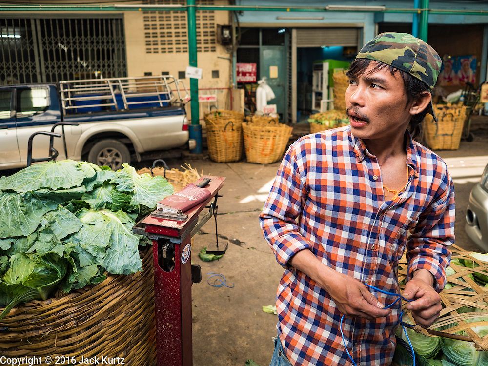 """11 AUGUST 2016 - BANGKOK, THAILAND:  A worker packs just delivered cabbage in the produce section of Pak Khlong Talat in Bangkok. Pak Khlong Talat (literally """"the market at the mouth of the canal"""") is the best known flower market in Thailand. It is the largest flower market in Bangkok. Most of the shop owners in the market sell wholesale to florist shops in Bangkok or to vendors who sell flower garlands, lotus buds and other floral supplies at the entrances to temples throughout Bangkok. There is also a fruit and produce market which specializes in fresh vegetables and fruit on the site. It is one of Bangkok's busiest markets and has become a popular tourist attraction.         PHOTO BY JACK KURTZ"""