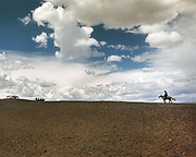 Under a wide blue sky with clouds, a horserider arrives at a Nadaam horserace, a traditional 20 Km speed race. <br /> Winning a race is quite the feat and prizes for winners include horses, and sometimes cars.