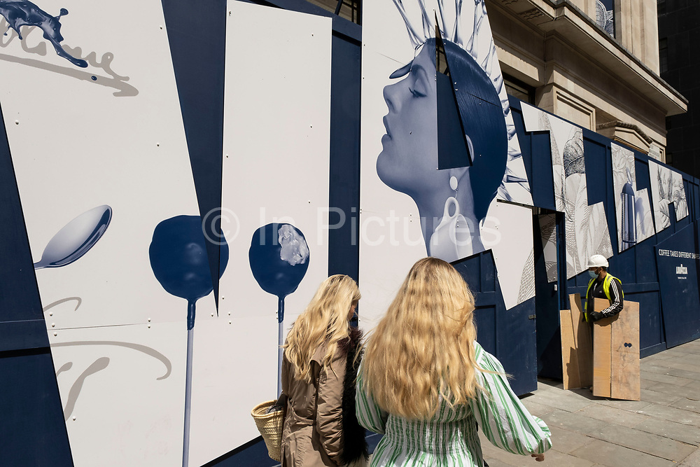 Passing people interact with a large scale hoarding for the coffee company Lavazza depicting a female characters head on 26th May 2021 in London, United Kingdom. Lavazza is an Italian manufacturer of coffee products. Founded in Turin in 1895 by Luigi Lavazza.