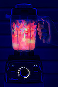 A hand holds a Vitamix blender as it mixes its glowing contents. Blacklight photography.