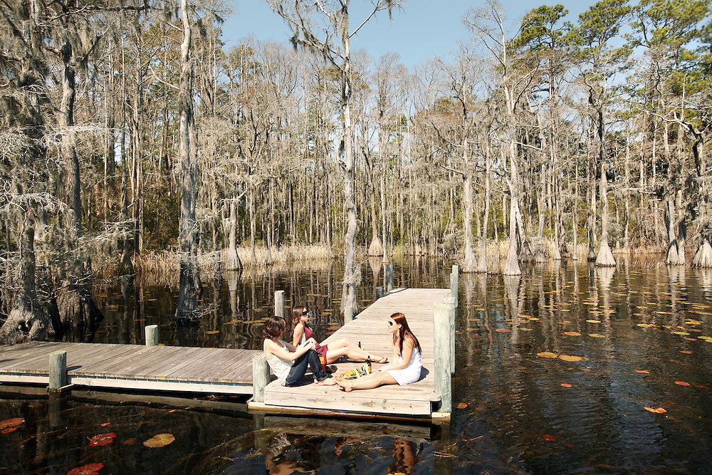 Lunch at the lake, Brunswick County, NC. Leah, Amy and Erin on a dock surrounded by Cyprus trees, Spanish Moss, and lily pads.