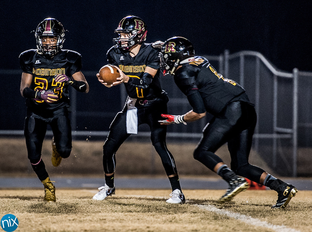 Jay M. Robinson's Josh Dale (7) prepares to hand the ball off to Que Reid (1) against Ashbrook during the first round of the NCHSAA Class 3AA state playoffs Friday night at Jay M. Robinson High School in Concord Friday night.