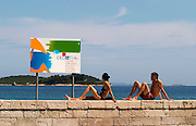 A young woman in bikini on a wall looking away and a young man in swimming trunks, a sign saying Welcome to Croatia, on the beach by the blue sea, and island in the background Orebic town, holiday resort on the south coast of the Peljesac peninsula. Orebic town. Peljesac peninsula. Dalmatian Coast, Croatia, Europe.