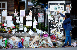 © Licensed to London News Pictures. 12/07/2017. LONDON, UK. Residents hold a vigil at the memorial wall by Latimer Station, west London, on Wednesday 12 July, 2017, to remember those killed in the Grenfell Tower fire four weeks on from the tragedy when around 80 people are thought to have been killed. Photo credit: ISABEL INFANTES/LNP