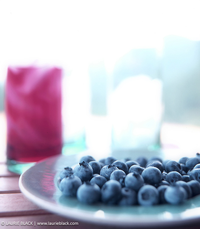 Dreamy platter of blueberries on porch table with juice glasses.
