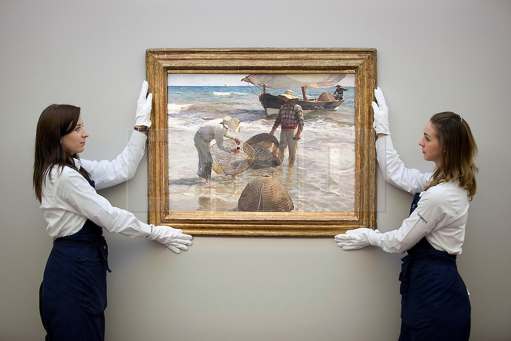 © Licensed to London News Pictures. 16/11/2012. London, UK. Two Sotheby's employees hold 'Pescadores Valencianos' (1895) (est. GB£1.000.000-1,500,000), a painting by Spanish artist Joaquin Sorolla, at a press call taking place at the London based auction house's New Bond Street premises today (16/11/12).  The sale, featuring works by 19th century European painters, is set to take place on the 20th of November. Photo credit: Matt Cetti-Roberts/LNP