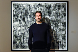 "© Licensed to London News Pictures. 26/02/2020. LONDON, UK. Artist Idris Khan poses with his work called ""Numbers - a hand sewn photograph"", 2019 (Starting price GBP20,000).  Preview of ""Human Touch"", an exhibition of one-of-a-kind artworks by international contemporary artists in collaborations with stitchers in British prisons.  In association with the charity Fine Cell Work, the artworks are on show at Sotheby's New Bond Street 26 February to 3 March 2020.  Photo credit: Stephen Chung/LNP"