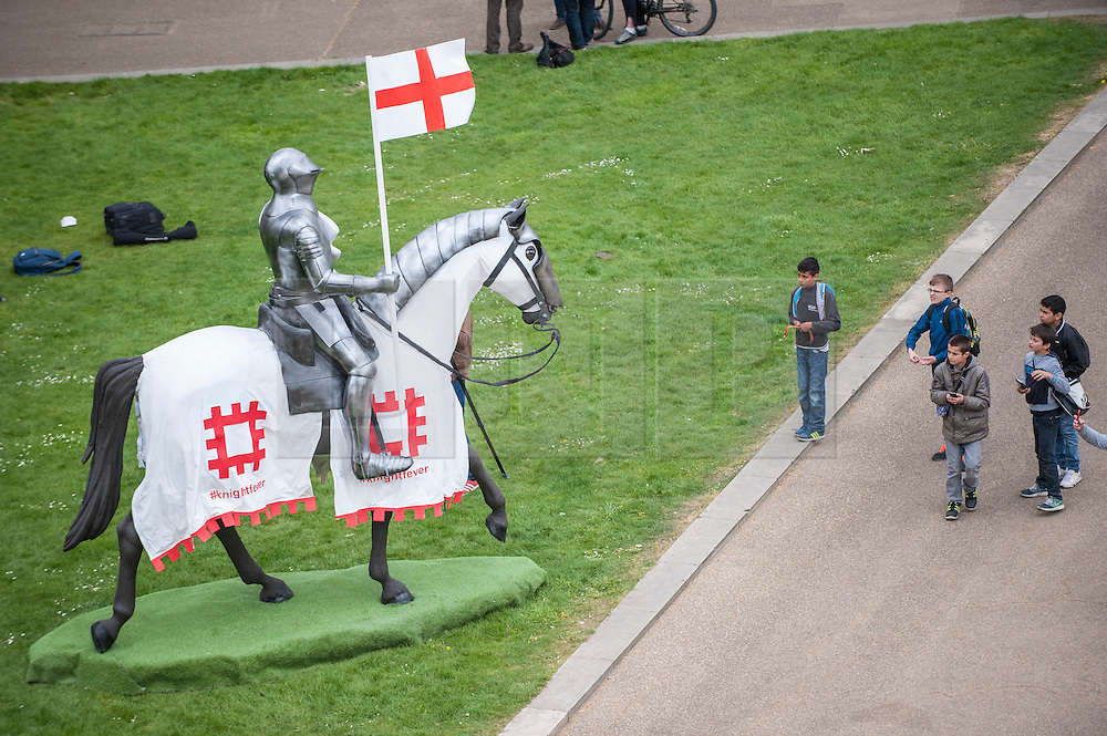 © Licensed to London News Pictures. 22/04/2015. Wellington Arch, London. A group of boys meet the 15ft St George at Wellington Arch, unveiled by English Heritage, in honour of the Patron Saint, ahead of England's largest St George's Day celebration at Wrest Park as well as the launch of a nationwide tour which will see the knight open jousting tournaments at castles across England. Photo credit : Stephen Chung/LNP
