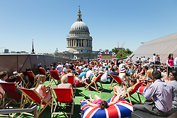 © Licensed to London News Pictures. 30/06/2015. London, UK. People relax in deckcharis and cushions as they watch Wimbledon tennis on a big outdoor screen during hot and sunny weather near St Paul's Cathedral in London today. Photo credit : Vickie Flores/LNP