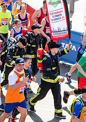 © Licensed to London News Pictures. 22/04/2018. London, UK. Firemen that tackled the Grenfell Tower Fire pass the Cutty Sark in Greenwich during the Virgin Money London Marathon 2018. Photo credit: Rob Pinney/LNP