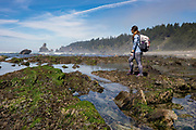 Female hiker along the tide pools at Shi Shi beach on the Olympic coast in Washington. Photo by Brandon Alms Photography
