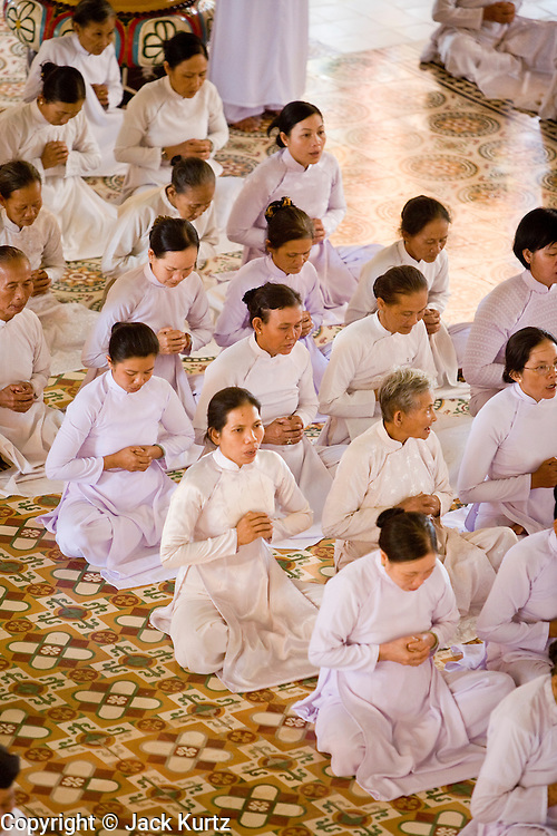"""10 MARCH 2006 - TAY NINH, VIETNAM: Noon prayers at the Cao Dai Main temple in Tay Ninh. The Cao Dai complex in Tay Ninh is the sect's headquarters. The Cao Dai religion is a blending of Buddhism, Confucianism, Taoism, Christianity and Islam. There """"saints""""  include Chinese leader Sun Yat Sen and French author Victor Hugo. There are about two million members of the Cao Dai religion in Vietnam. British author Graham Greene, who wrote about the Cao Dai in the """"The Quiet American"""" said the relegion was """"a Walt Disney fantasia of the East."""" Photo by Jack Kurtz / ZUMA Press"""