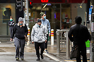 Melbourne locals with masks under their chins walk across an intersection in the CBD during COVID-19 in Melbourne, Australia. Victoria has recorded 14 COVID related deaths including a 20 year old, marking the youngest to die from Coronavirus in Australia, and an additional 372 new cases overnight. (Photo by Dave Hewison/Speed Media)