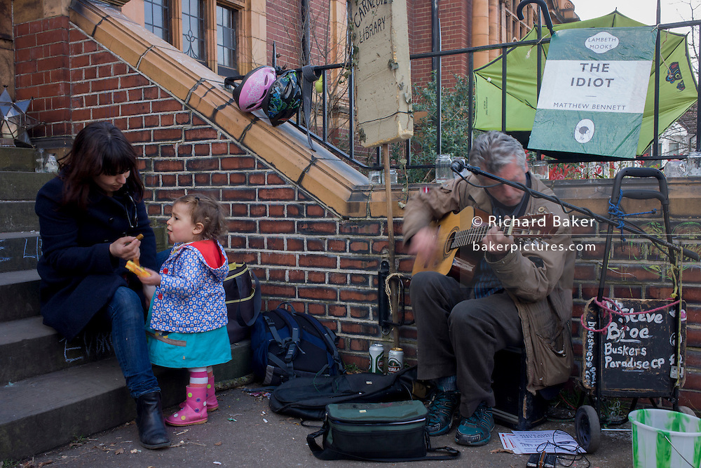 A young girl and mother listen to a musician outside Carnegie Library in Herne Hill, south London while occupiers remain inside the premises on day 6 of its occupation, 5th April 2016. The angry local community in the south London borough have occupied their important resource for learning and social hub for the weekend. After a long campaign by locals, Lambeth have gone ahead and closed the library's doors for the last time because they say, cuts to their budget mean millions must be saved.