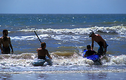 Pair of children learning how to kayak in the ocean in Galveston, Texas