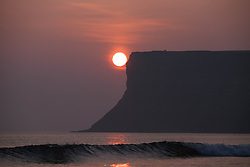 © Licensed to London News Pictures. <br /> 10/04/2015. <br /> <br /> Saltburn, United Kingdom<br /> <br /> The sun climbs up above the horizon into the morning sky during a dramatic sunrise over Huntcliff near Saltburn.<br /> <br /> Photo credit : Ian Forsyth/LNP
