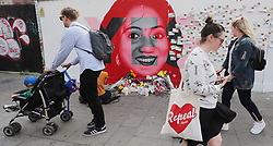 People pass a mural of Savita Halappanavar in Dublin as votes are counted in the referendum on the 8th Amendment of the Irish Constitution which prohibits abortions unless a mother's life is in danger.