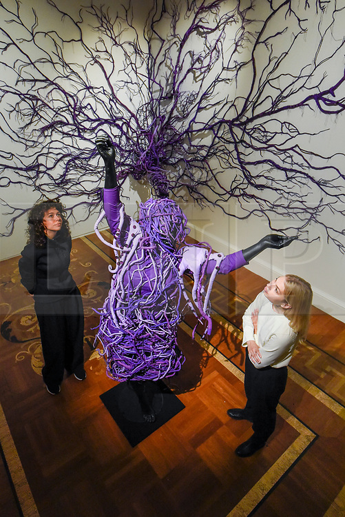 """© Licensed to London News Pictures. 29/09/2019. LONDON, UK.  Staff members pose with """"A Reversed Retrogress Scene 2"""", 2013, by Mary Sibande. Preview of """"Mary Sibande:  I Came Apart at the Seams"""", an exhibition of one of South Africa's moist prominent artists, Mary Sibande.  Her first solo UK exhibition included photographs and sculptural works challenging stereotypical depictions of woman in South Africa today.  The show is in on with 1-54 Contemporary African Art Fair at Somerset House 3 October to 5 January 2020.  Photo credit: Stephen Chung/LNP"""