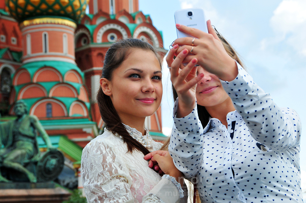 Visitors pose for photographs with St. Basil's Cathedral of Moscow in the background. The structure, now a museum, was built in the mid-1500's. Part of the Kremlin and Red Square UNESCO World Heritage site, the cathedral is without a doubt the most recognizable Orthodox Christian church in the world.