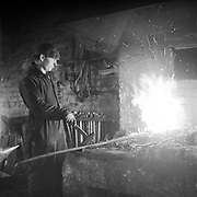 An employee of Savonseutu cooperatives repair shop heating up a piece of metal in a forge. 1955