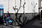 Lady cyclist reads Barclays-sponsored bike rental instructions with shadows of bare branches on white wall.