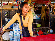 """14 FEBRUARY 2019 - SIHANOUKVILLE, CAMBODIA: A Cambodian woman who moved to Sihanoukville with her family in her snack stand on a construction site in Sihanoukville. She said they moved to Sihanoukville about a month ago hoping to find jobs in the Chinese financed boom in Sihanoukville. Her husband works as a construction laborer and she runs a small drink and snack stand. There are about 80 Chinese casinos and resort hotels open in Sihanoukville and dozens more under construction. The casinos are changing the city, once a sleepy port on Southeast Asia's """"backpacker trail"""" into a booming city. The change is coming with a cost though. Many Cambodian residents of Sihanoukville  have lost their homes to make way for the casinos and the jobs are going to Chinese workers, brought in to build casinos and work in the casinos.      PHOTO BY JACK KURTZ"""
