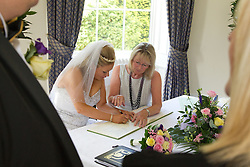 Visually impaired bride being helped to sign register by the registrar.
