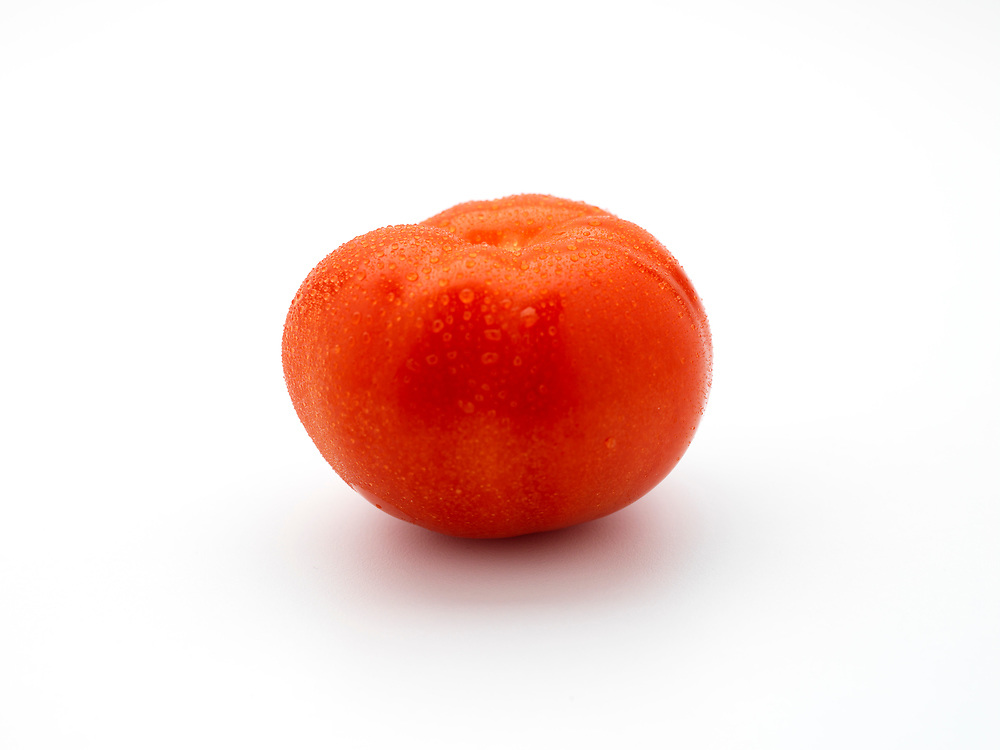 Single red tomato on a white background