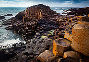 The Giant's Causeway (known in Irish as Clochán an Aifir or Clochán na bhFómharach) is an area of about 40,000 interlocking basalt columns, the result of an ancient volcanic eruption. It is located in County Antrim on the northeast coast of Northern Ireland, about three miles (4.8 km) northeast of the town of Bushmills. It was declared a World Heritage Site by UNESCO in 1986, and a National Nature Reserve in 1987 by the Department of the Environment for Northern Ireland. In a 2005 poll of Radio Times readers, the Giant's Causeway was named as the fourth greatest natural wonder in the United Kingdom. The tops of the columns form stepping stones that lead from the cliff foot and disappear under the sea. Most of the columns are hexagonal, although there are also some with four, five, seven and eight sides. The tallest are about 12 metres (39 ft) high, and the solidified lava in the cliffs is 28 metres thick in places.