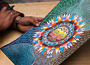 Colorful sun art is crafted and sold at Otavalo market, Ecuador, South America. The culturally vibrant town of Otavalo attracts many tourists to a valley of the Imbabura Province of Ecuador, surrounded by the peaks of Imbabura 4,610m, Cotacachi 4,995m, and Mojanda volcanoes. The indigenous Otavaleños are famous for weaving textiles, usually made of wool, which are sold at the famous Saturday market and smaller markets during the rest of the week. The Plaza del Ponchos and many shops tantalize buyers with a wide array of handicrafts. Nearby villages and towns are also famous for particular crafts: Cotacachi, the center of Ecuador's leather industry, is known for its polished calf skins; and San Antonio specializes in wood carving of statues, picture frames and furniture. Otavaliña women traditionally wear distinctive white embroidered blouses, with flared lace sleeves, and black or dark over skirts, with cream or white under skirts. Long hair is tied back with a 3cm band of woven multi colored material, often matching the band which is wound several times around their waists. They usually have many strings of gold beads around their necks, and matching tightly wound long strings of coral beads around each wrist. Men wear white trousers, and dark blue ponchos. Otavalo is also known for its Inca-influenced traditional music (sometimes known as Andean New Age) and musicians who travel around the world.