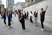Asian tourist group of young people perform an impromptu dance routine in Trafalgar Square in London, United Kingdom.