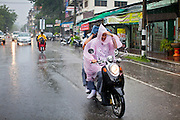 24 JUNE 2011 - CHIANG MAI, THAILAND: People ride motorcycles through a rainstorm in central Chiang Mai, Thailand.  PHOTO BY JACK KURTZ