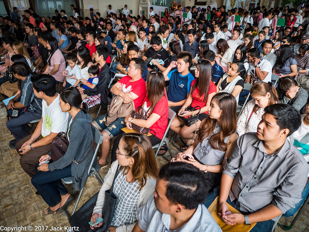 """14 FEBRUARY 2017 - BANGKOK, THAILAND: People wait to get register their marriages in the Bang Rak district in Bangkok. Bang Rak is a popular neighborhood for weddings in Bangkok because it translates as """"Village of Love."""" (Bang translates as village, Rak translates as love.) Hundreds of couples get married in the district on Valentine's Day, which, despite its Catholic origins, is widely celebrated in Thailand.      PHOTO BY JACK KURTZ"""