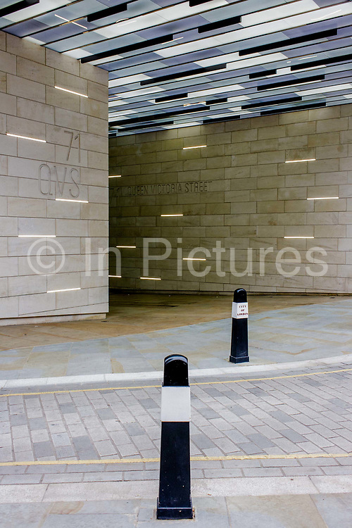 Modernist architecture at the entrance of 71 Queen Victoria Street on the corner with Trinity Lane EC4 in the City of London. The visual theme to this landscape is that of horizontal black and white lines that are echoed in the light built into the building's walls and ceiling and in the street's traffic bollards.