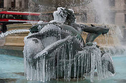 © Licensed to London News Pictures. 09/02/2021. LONDON, UK. Ice covered frozen fountains in Trafalgar Square during light snow flurries as the cold weather brought on by Storm Darcy continues.  Photo credit: Stephen Chung/LNP