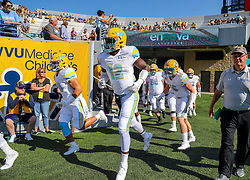 Sep 11, 2021; Morgantown, West Virginia, USA; Long Island Sharks defensive lineman Ben Waibogha (12) leads his team out onto the field prior to their game against the West Virginia Mountaineers at Mountaineer Field at Milan Puskar Stadium. Mandatory Credit: Ben Queen-USA TODAY Sports