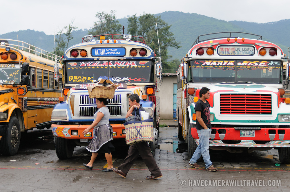Passengers walk in front of parked chicken buses behind the Mercado Municipal (town market) in Antigua, Guatemala. From this extensive central bus interchange the routes radiate out across Guatemala. Often brightly painted, the chicken buses are retrofitted American school buses and provide a cheap mode of transport throughout the country.