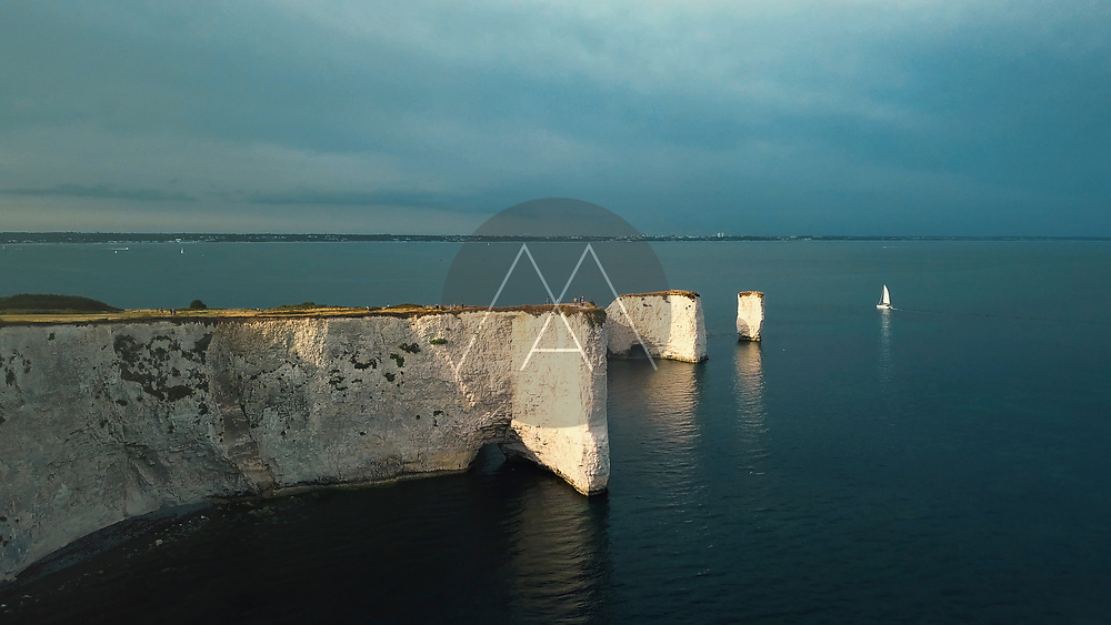 Aerial view of the Old Harry Rocks landmark with white cliffs lit by the late afternoon Sun light in Studland, Dorset, United Kingdom.
