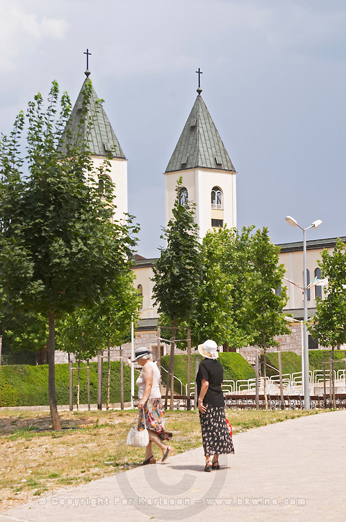 The church, two old ladies in sun hats and flowery skirts. Medugorje pilgrimage village, near Mostar. Medjugorje. Federation Bosne i Hercegovine. Bosnia Herzegovina, Europe.