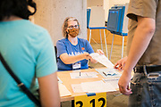 An election official hands out ballots to voters at a polling location in Downtown Minneapolis, Minnesota, U.S., on Tuesday, Aug. 11, 2020. Photographer: Ben Brewer/Bloomberg