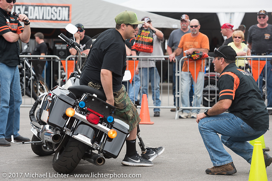 Al Rapaso of Big Als Cycles in San Francisco, CA shows Harley-Davidson Regional Police Rep Rob Grimsley his technique for picking up a bike at the Harley-Davidson display at the Daytona Speedway during Daytona Bike Week. Daytona Beach, FL. USA. Monday March 13, 2017. Photography ©2017 Michael Lichter.