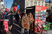 Two women wearing matching coats walk in winter sunshine opposite the Ritz Hotel on Piccadilly in central London, on 11th February 2020, in London, England.