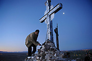 """pvc042211d/4-22-11/asec.  A short while before the day's first rays of sunlight, Joseph Ernest Barela (CQ), of Albuquerque, places a single long stemmed rose into the base of a cross at the peak of Tome Hill on Good Friday, photographed Friday April 22, 2011.  Barela said he is recovering from a cocaine and alcohol addiction, made the pilgrimage to Tome and said """"The only thing that's gonna keep me clean is Jesus and The Lord.""""  (Pat Vasquez-Cunningham/Journal)"""