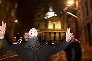Masked protester saletes outside St Paul's as eviction of the Occupy London OLSX camp takes place. The anti-capitalist demonstration that saw protesters camp outside St Paul's Cathedral in London was brought to an end by bailiffs and police. Protesters staging Occupy London were refused permission by the Court of Appeal last week to challenge orders evicting them from the cathedral steps, where they had been living in tents since October 15 last year. The City of London Corporation called on protesters to remove their tents voluntarily, but around 50 or 60 refused to budge. Some protesters created makeshift barriers out of wooden shelving units as police moved in to help bailiffs clear the camp. Police said 20 people had been arrested but the operation was largely peaceful.