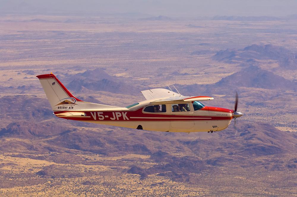 A Desert Air Cessna 210 flies above the Namib Desert, Namibia