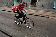 Een meisje fietst in de regen door de Vijzelstraat in Amsterdam.<br /> <br /> A girl is cycling in the rain at the Vijzelstraat in Amsterdam