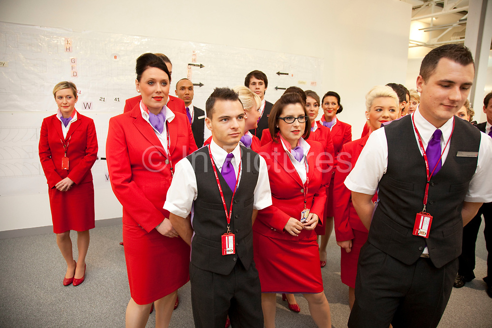 Just one week away from getting their 'wings' these flight attendants proudly wear their red uniforms as they prepare for an in flight training session. Virgin Atlantic air stewardess and steward training at The Base training facility in Crawley. Potential hostesses are put through a gruelling 6 week training program, during which they are tested to their limits. With exams every day requiring an 88% score to pass. The Base is a modern environment for a state of the art airline training situated next to Virgin Atlantic's HQ.