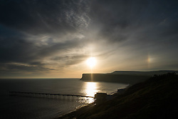 © Licensed to London News Pictures. <br /> 07/04/2015. <br /> <br /> Saltburn, United Kingdom<br /> <br /> A Partial 22 degree Sun Halo can be seen over Huntcliff in Saltburn, Cleveland. Sun halos are a sign of high thin cirrus clouds drifting 20,000 feet or more above the ground. The halos are caused by both refraction, or splitting of light, and also by reflection, or glints of light from these ice crystals.<br /> <br /> Photo credit : Ian Forsyth/LNP
