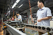 Workers operate on the assembly line for flat screen display at a TCL Corp. factory in Huizhou, Guangdong province, China, on Monday, April 18, 2016. Once synonymous with Chinas manufacturing might, as the days of cheap land and labor recede, the provinces businesses are in a race to upgrade or move.